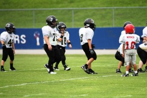 Tiger Pewee quarterback, Briz Trapp, leads his team to the line in Saturday's Boys to Men Jamboree in McMinnville.