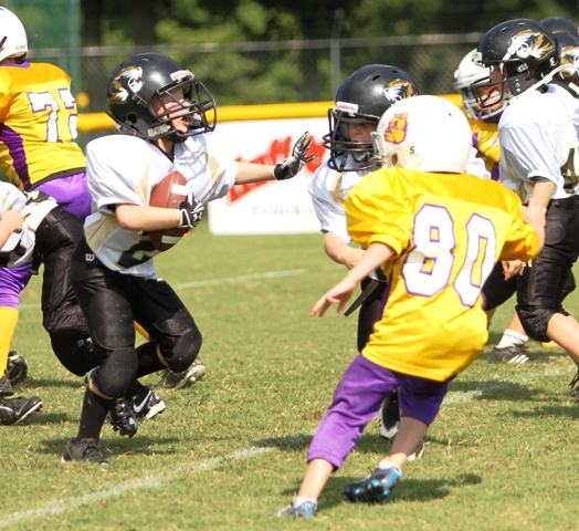 Seth Cantrell moves a Fentress County Bulldog out of the way in the Peewee Tigers Black Team scrimmage last Saturday.