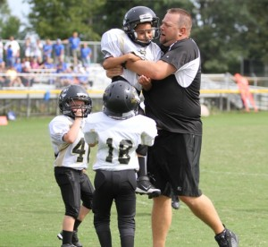 Peewee head coach, Brad Trapp, celebrates with Marquez Chalfant after his game winning touchdown Sunday.