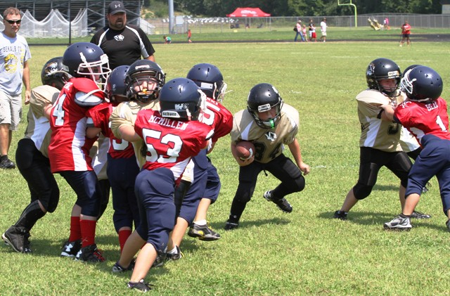 The Peewee Offensive Line opens up a hole for Tiger Quarterback, Wesley Kent in Saturday's Jamboree